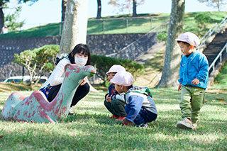写真:保育園の先生と園児たちが公園で遊んでいる